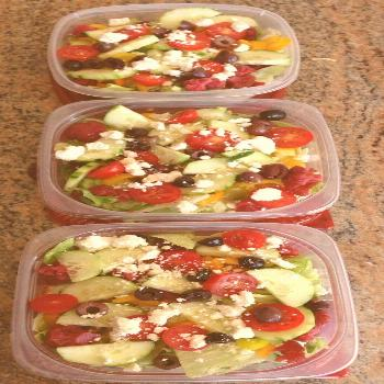 Meal prep for the week. Greek salads: lettuce, cherry tomatoes, cucumbers, peppe...